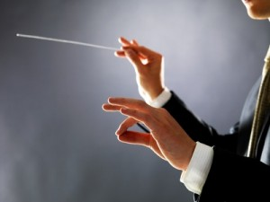 Cropped image of a male orchestra conductor directing with his baton in concert